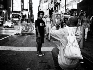 father taking snapshot of son in Times Square