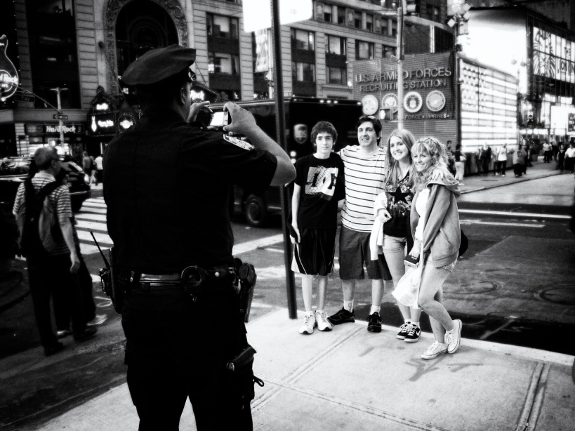 NYC cop taking a family's picture in Times Square