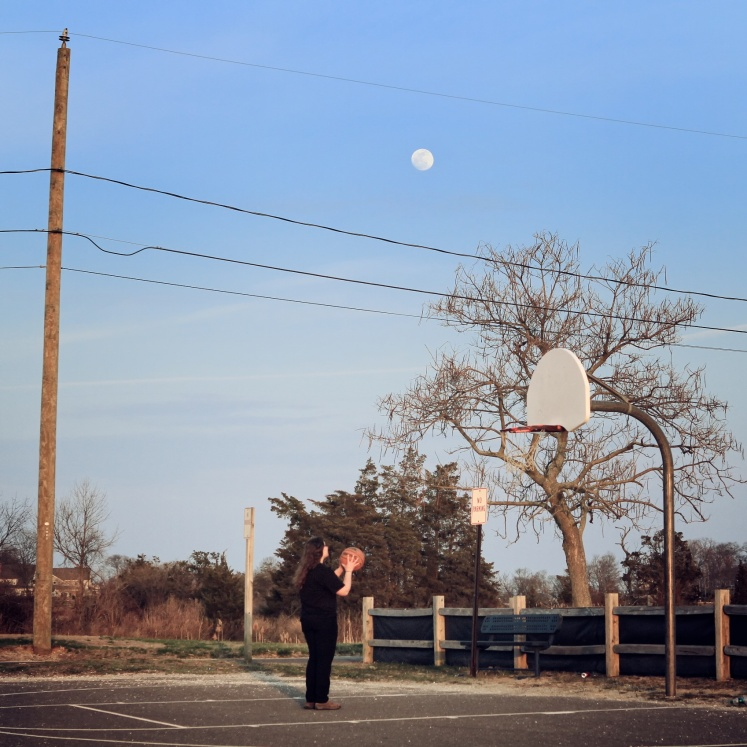 Girl playing basketball under full moon