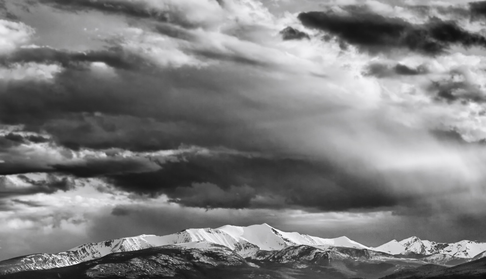 Clouds over snow-capped mountains