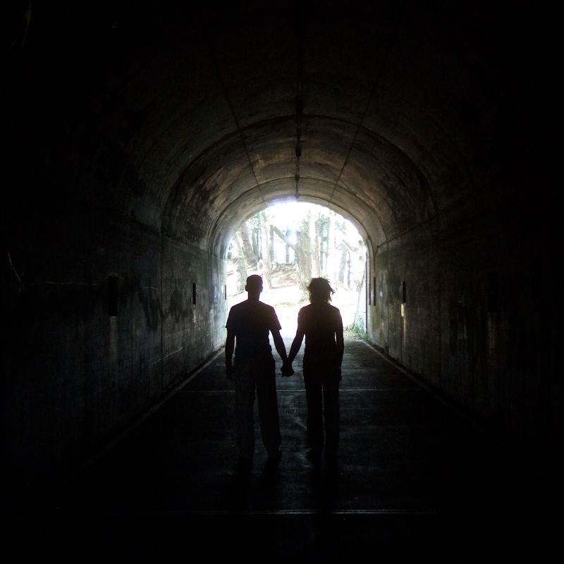 two people in dark tunnel