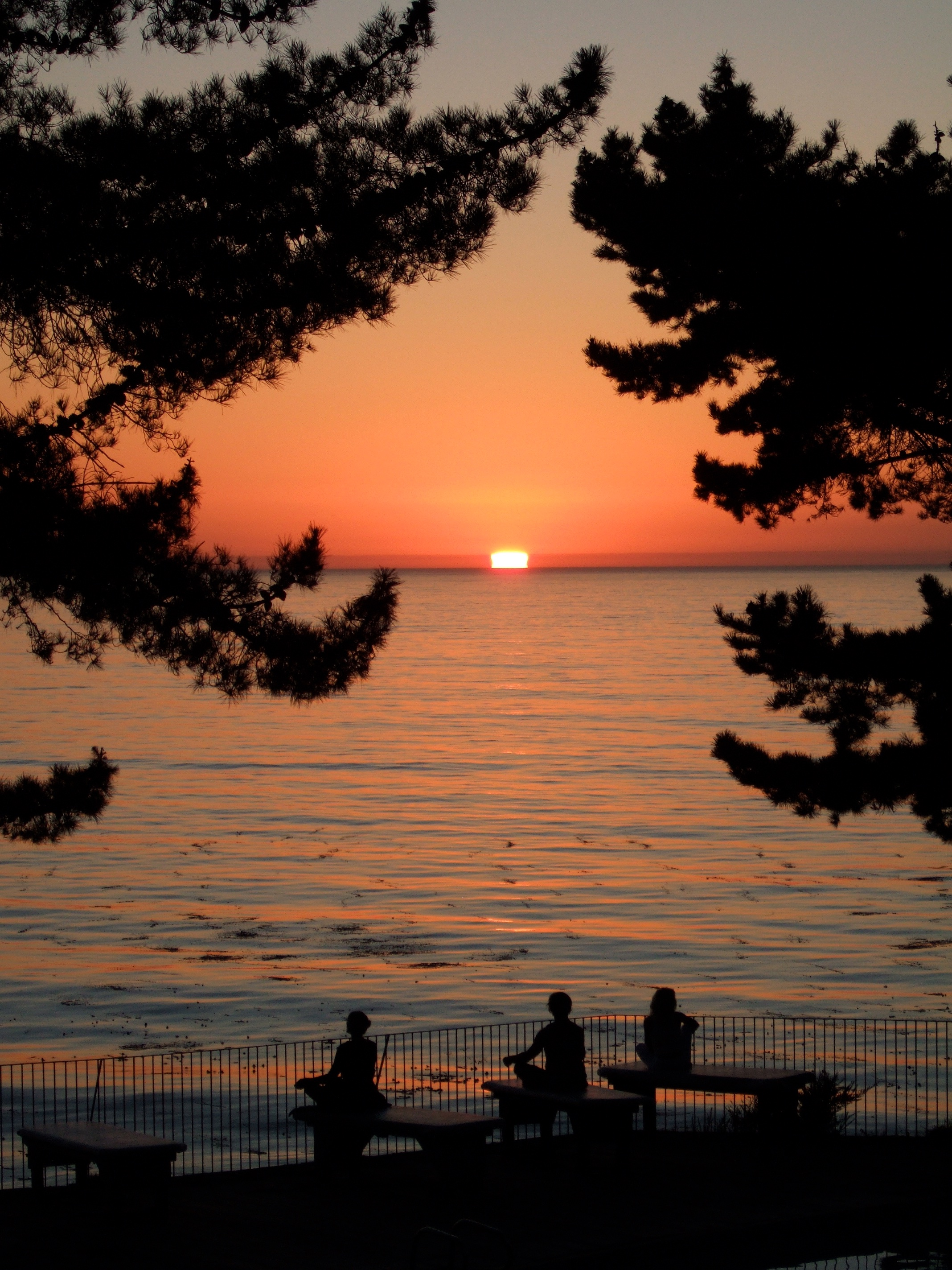 People meditating at sunset