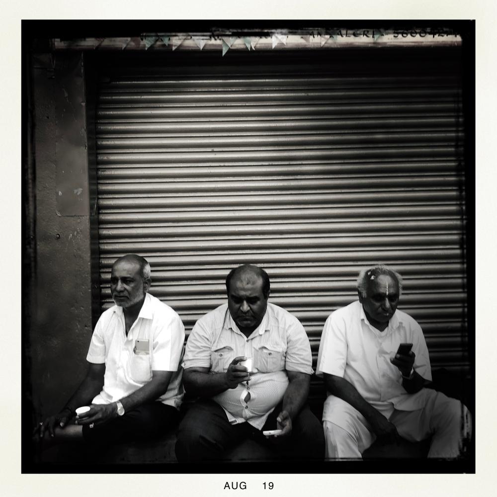 3 men sitting along shop window