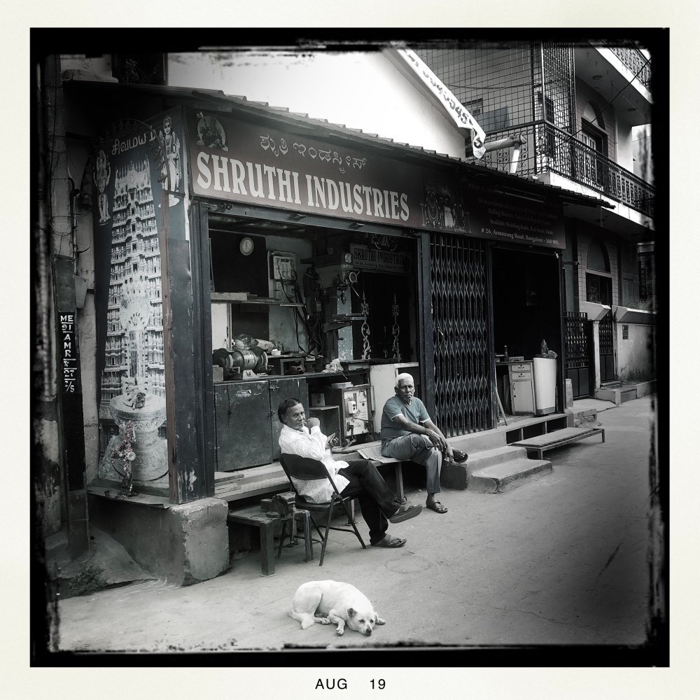 Old men and dog in front of shop