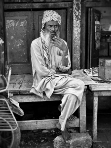 Old man sitting in alley in India